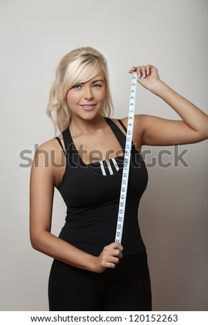 Beautiful woman holding a  measuring tape looking at camera as if to say how big