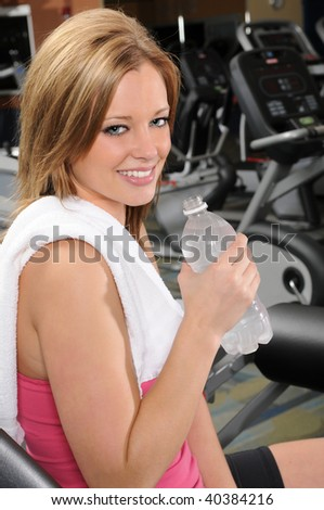 Beautiful woman holding bottled water at the gym