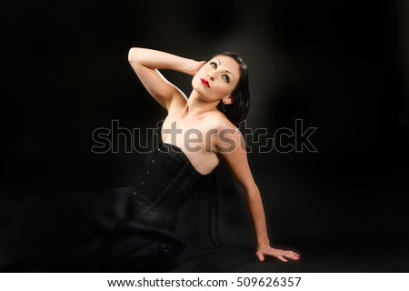 beautiful woman in a black bustier on a black background.  She has the look of a classic movie star.