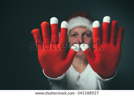 Beautiful woman in Santa Claus costume making Stop hand sign, retro toned image with selective focus