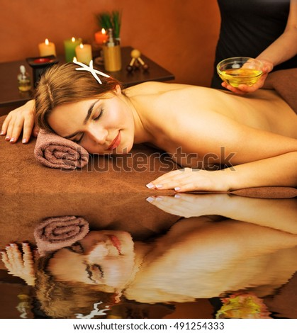 Beautiful woman in spa salon having spa therapy aroma oil procedure with hands of masseur water reflection