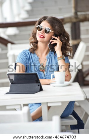 Beautiful woman in sunglasses using tablet at cafe. Woman drinking cappuccino coffee in the summer outdoor cafes.