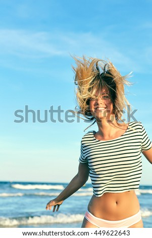 Beautiful woman in swimsuit jumping near the sea. Blonde girl in bikini having fun on vacation. Young woman shakes her hair on a background of the blue ocean.