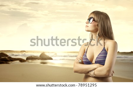 Beautiful woman in swimsuit with seaside in the background