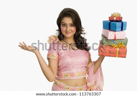 Beautiful woman in traditional dress holding gifts and smiling