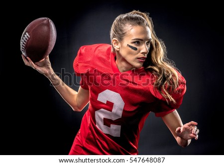 Beautiful woman in uniform playing american football with ball on black