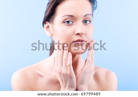 beautiful woman is looking at camera and touching her face on blue background