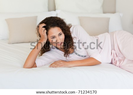 Beautiful woman lying down on her bed at home