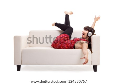 Beautiful woman lying on the sofa and listen music with headphones, isolated on white