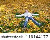 Beautiful woman making angels in bright  leaves mid autumn in idaho - stock photo