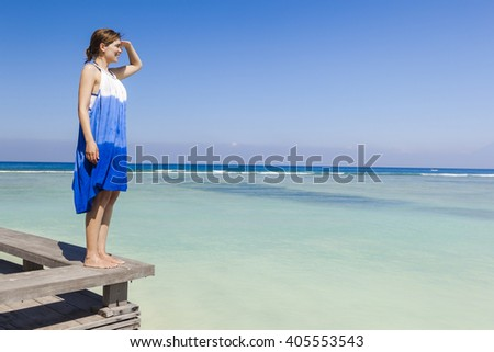 Beautiful woman on a beautiful tropical beach looking somewhere