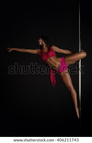 Beautiful woman performing pole dance on dark background