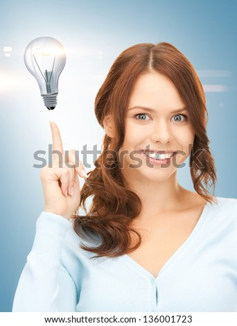 beautiful woman pointing her finger at light bulb