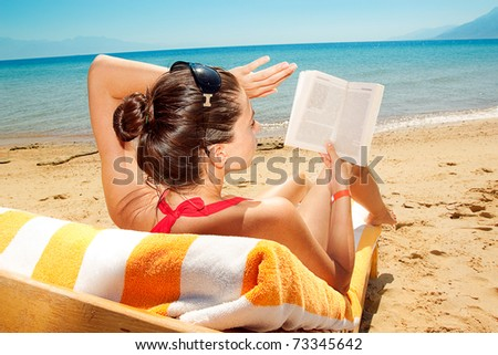 beautiful woman reading a book on background of beach