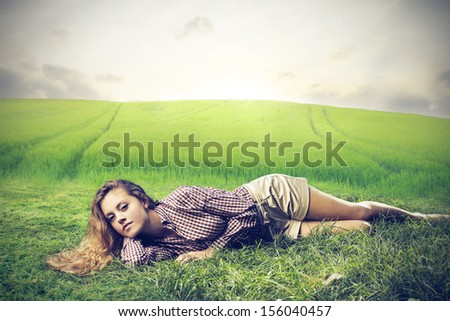 beautiful woman relaxes lying on the grass in the countryside