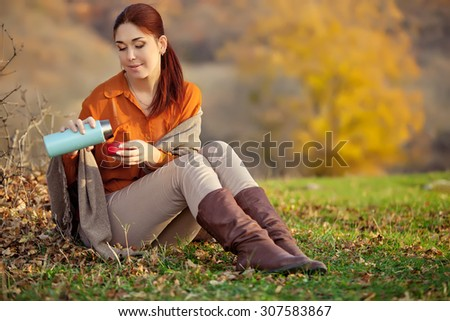 Beautiful woman relaxing and drinking coffee, sitting in autumn garden, wrapped in a blanket wool blanket.