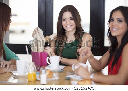 Beautiful woman showing her friends what she just bought