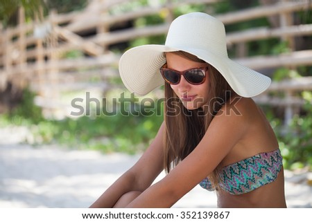 Beautiful woman sit on the sand at paradise beach