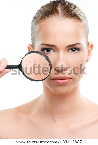 Beautiful woman, skin close up with a magnifying glass, over a white background
