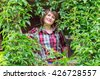 beautiful woman smiling on a background of green lianas - stock photo