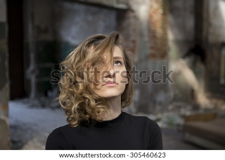Beautiful woman with a serious expression on her face looking up with a view of abandoned building in the background