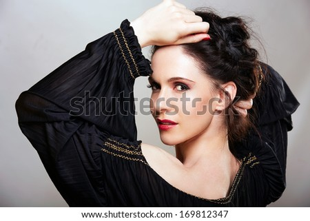 Beautiful woman with brown hair braided in upstyle wearing black off shoulder dress on studio background