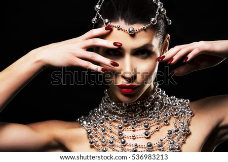 beautiful woman with dark makeup wearing blue and silver mask surrounded by party accessories on black background