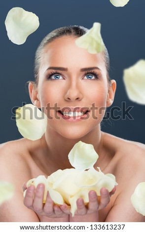 Beautiful woman with flower petals falling, close up over a dark  background