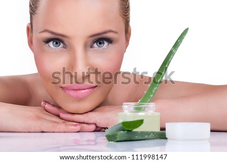 Beautiful woman with healthy skin posing next cream of aloe vera
