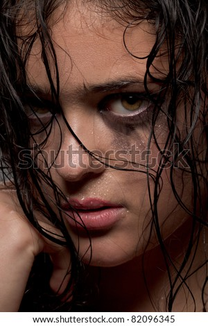 Beautiful woman with running eye make up and wet hair