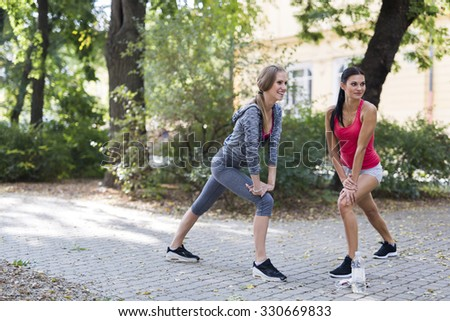 Beautiful women stretching outdoors before setting off for their run