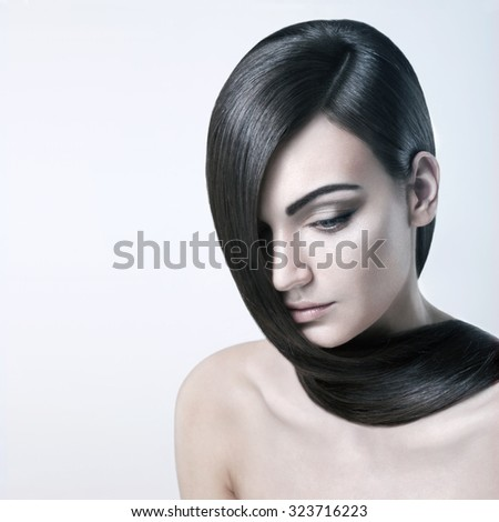 Beautiful yong woman with healthy skin and well groomed hair. Her hair runs on nude shoulders and she looks tranquil.