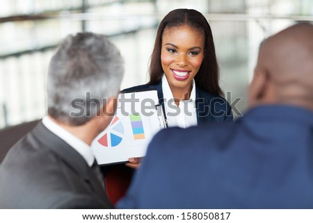 beautiful young african businesswoman explaining graph to business team