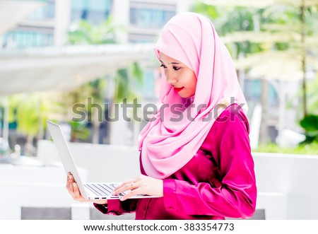 Beautiful young Asian Muslim woman wearing head scarf (hijab) working on a laptop outside the office.