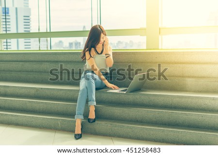 Beautiful Young Asian women using smartphone and a laptop computer sitting on the stairs with happiness and and concentrate.Vintage tone with city view background.
