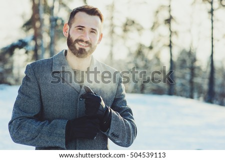 beautiful young bearded men relaxing on winter walk in snowy forest, candid capture, lifestyle scene