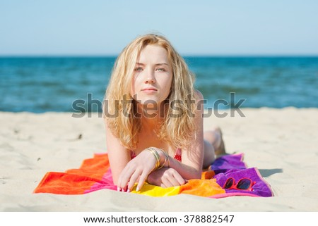Beautiful young blond woman lying on a beach - summer portrait