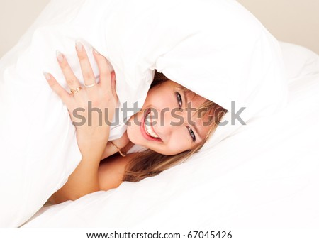 beautiful young blond woman under the blanket