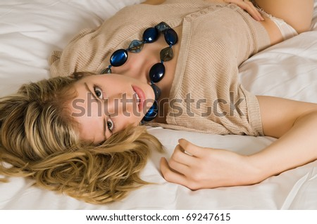 Beautiful young blonde in bed in a tan knit blouse