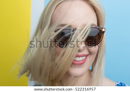 beautiful young blonde woman with elegant sunglasses posing in a studio. Fashion spring summer photo