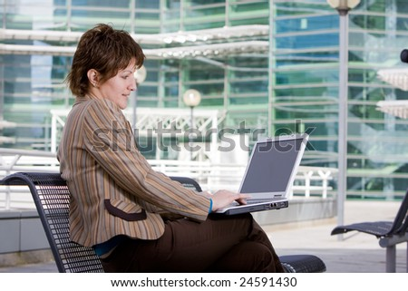 Beautiful young brunette woman using a computer laptop outdoors in front of an office building
