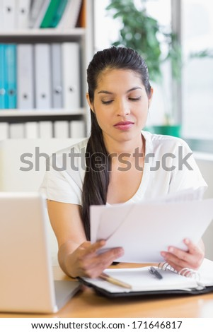 Beautiful young businesswoman reading documents at office desk