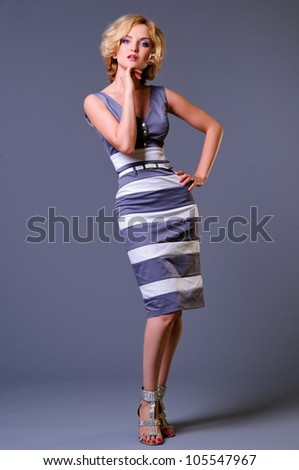 beautiful young businesswoman wearing a dress. in full growth. on a gray background