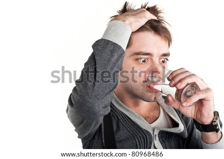 Beautiful young caucasian white guy standing in a gray dress and a hand on the head with a sad expression on his face holding a glass of water and drink from his isolation over white