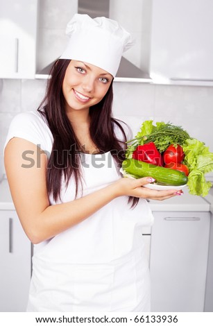 beautiful young cook with vegetables in the kitchen
