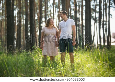 Beautiful young couple expecting baby walking at forest at summer day