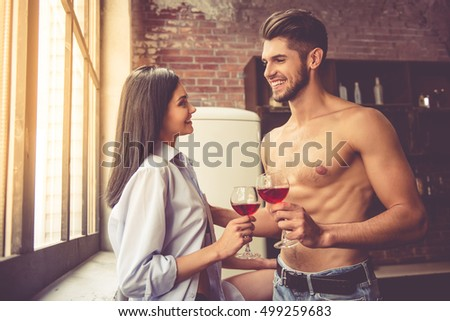 Beautiful young couple is looking at each other and smiling while drinking wine in kitchen at home