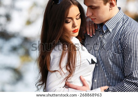 beautiful young couple posing in the park on a background of trees