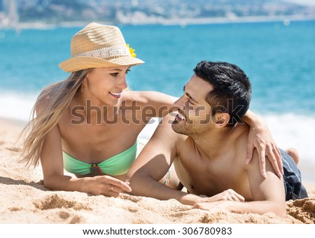 Beautiful  young couple sunbathing at sandy beach in vacation