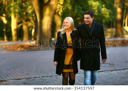 Beautiful young couple walking in the sunny autumn park and smiling brightly